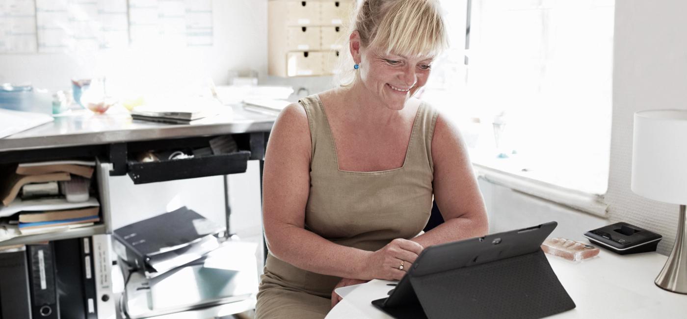 Billede af en kvinde der sidder med en tablet - Skriv til Gohosting CAMP